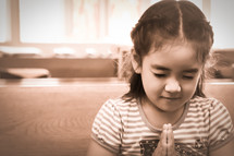 Girl with eyes closed and clasped hands in prayer.