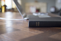 Holy Bible and laptop on a desk