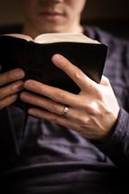 man reading a pocket Bible