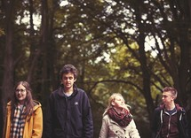 youth walking in a forest in coats