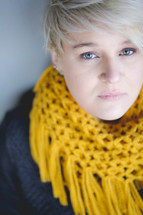 A blond woman wearing a bright yellow scarf.