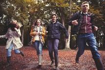 teens running through fall leaves outdoors