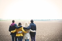 teens standing together in a field with their backs to the camera
