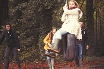 teens on a tire swing in a forest