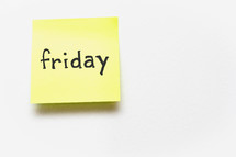 """A yellow sticky note with """"friday"""" written in black ink."""