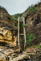 Wooden stairs leading down rocky hills to the beach.