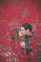 a couple kissing between branches covered with red berries