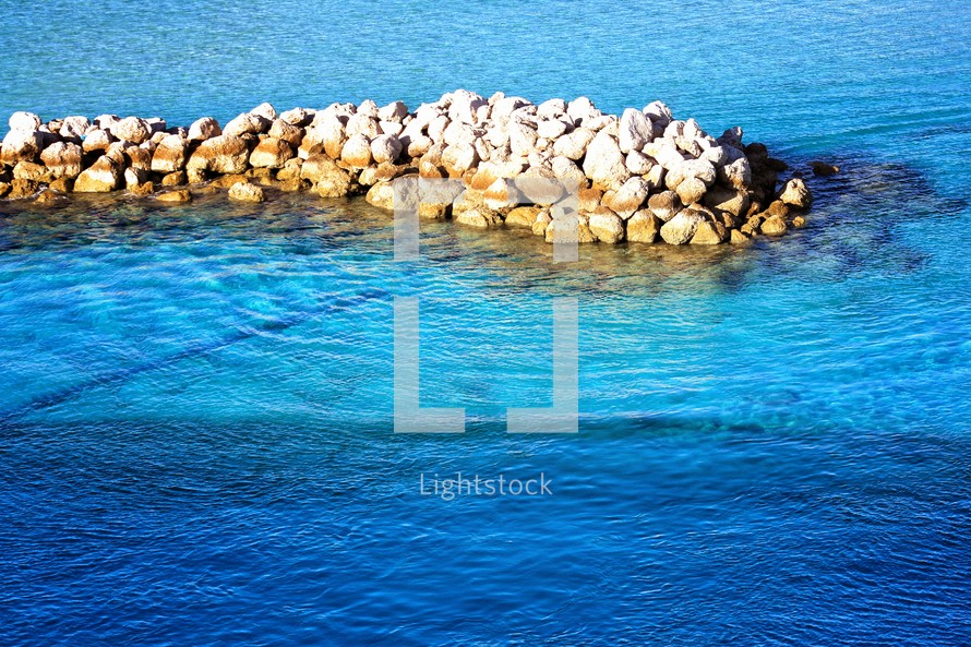 ice blue water against a rock jetty