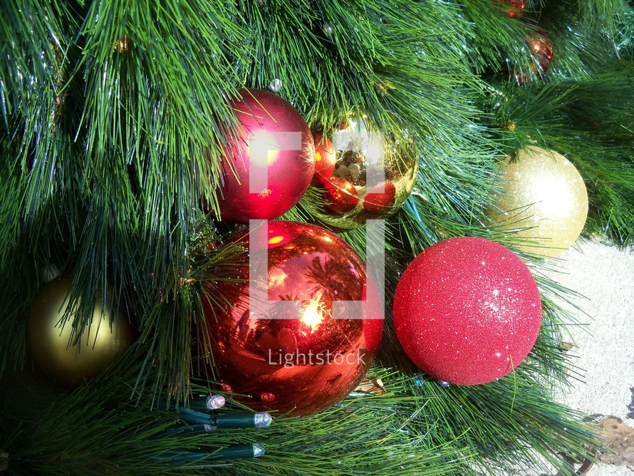Christmas Tree Ornaments reflecting memories of Christmas time for the family, children, neighbors and friends reflecting the glory of Jesus with green, red and gold Christmas ornaments and lights.