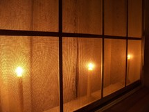 Christmas candles aglow in a window at night light up a home and make it feel warm and cozy during the winter months of Winter as we celebrate Christmas, Hanukkah and Jesus birthday.