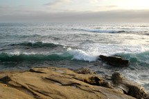Ocean waves crashing onto rocks on shore.