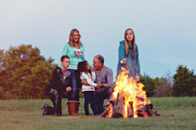 a family sitting by a campfire roasting marshmallows