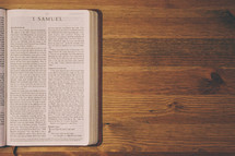 Bible on a wooden table open to the book of 1 Samuel.