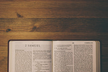 Bible on a wooden table open to the book of 2 Samuel.