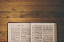 Bible on a wooden table open to the book of Ruth.