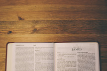 Bible on a wooden table open to the book of James.