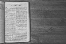 Bible on a wooden table open to the book of 2 Timothy.