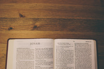 Bible on a wooden table open to the book of Jonah.