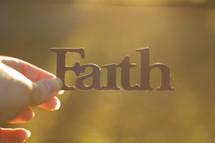 woman holding the word faith