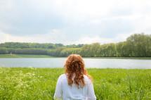 A woman walks through tall grass toward a lake.