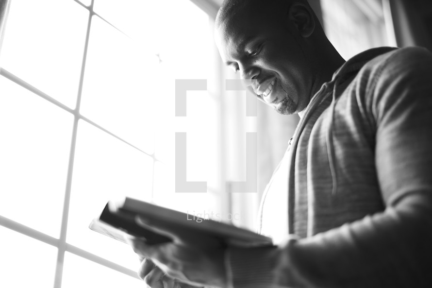 A man reading his Bible next to the window