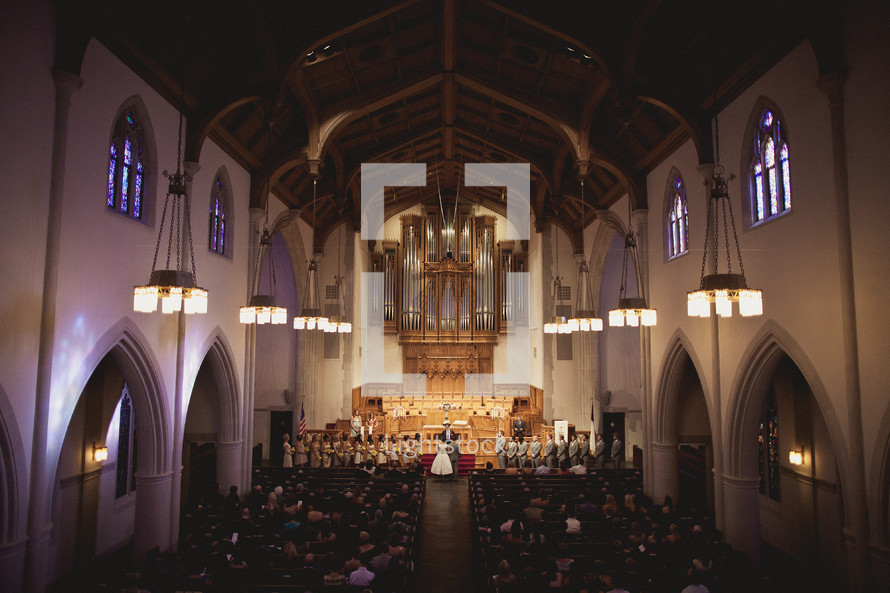 A filled chapel during a wedding ceremony