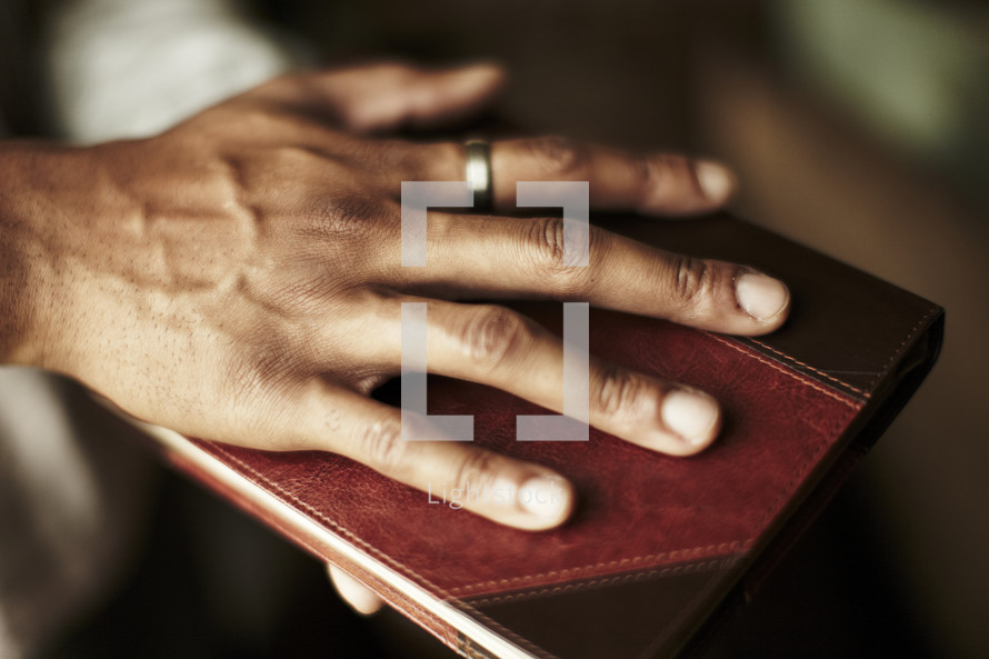 A man placing his hand on the front cover of a Bible