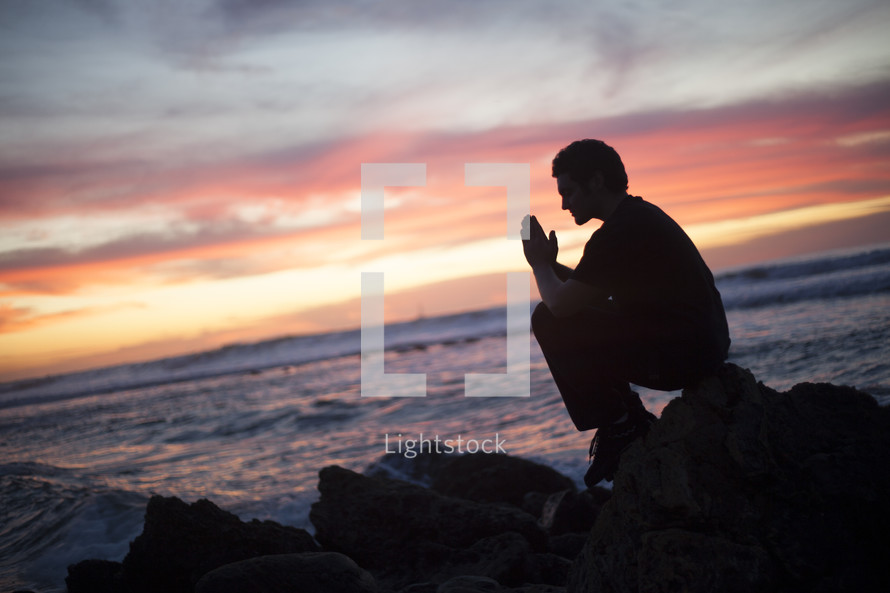 man in prayer sitting in prayer on a rock facing the ocean
