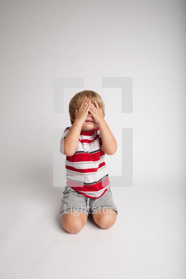 Little boy covering eyes