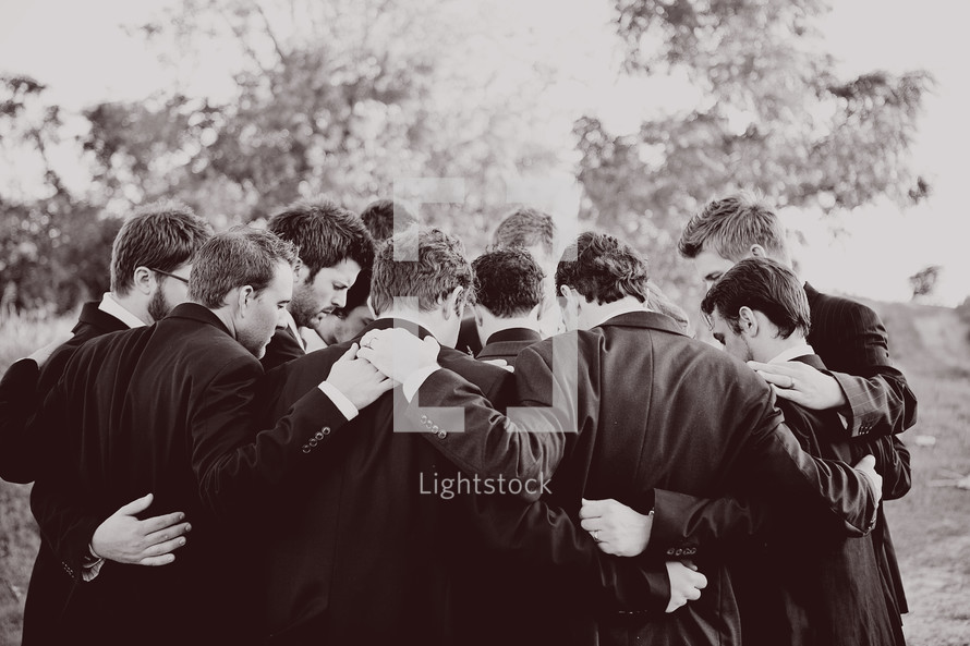 men in suits in a group prayer