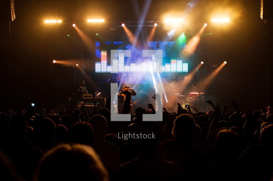 singer on stage at a concert under stage lights