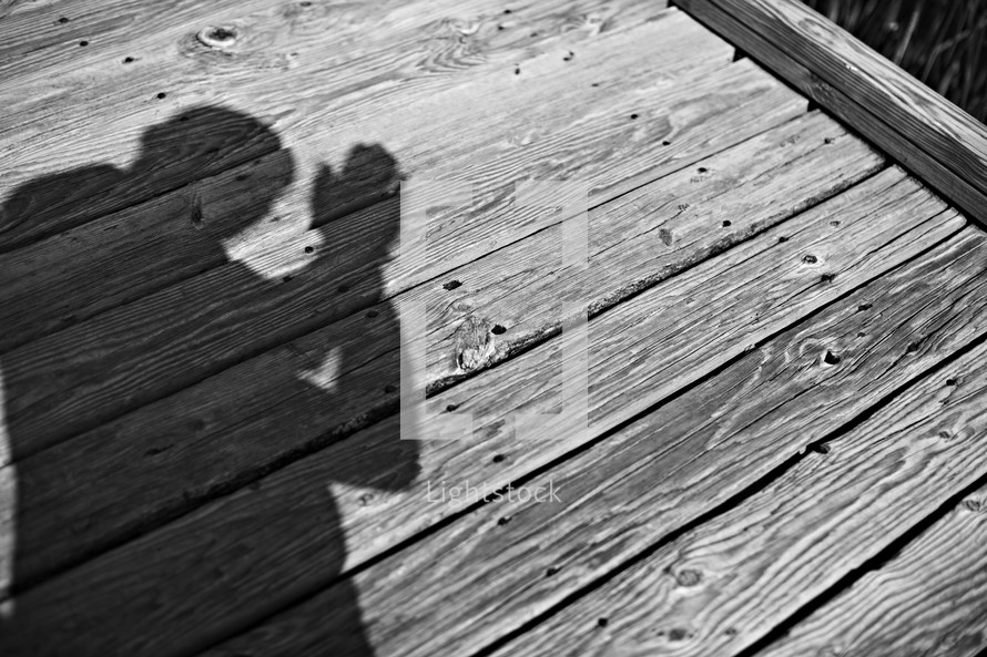 The shadow of a person praying on a dock