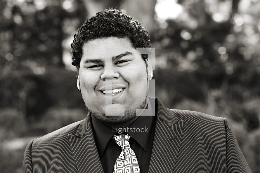A smiling young man in a shirt and tie Samoan