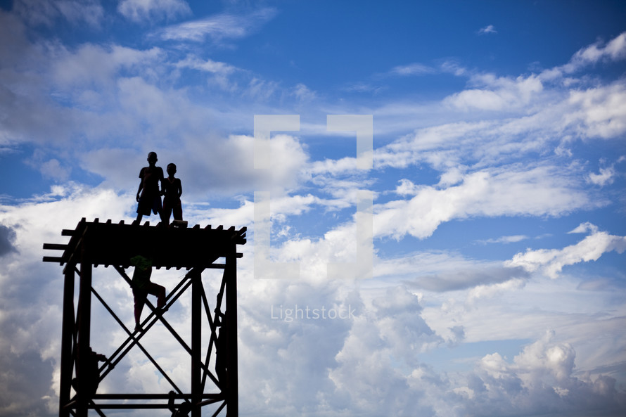 children climbing and standing on a roof under a blue sky