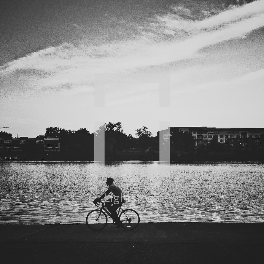 Man riding bicycle by lake
