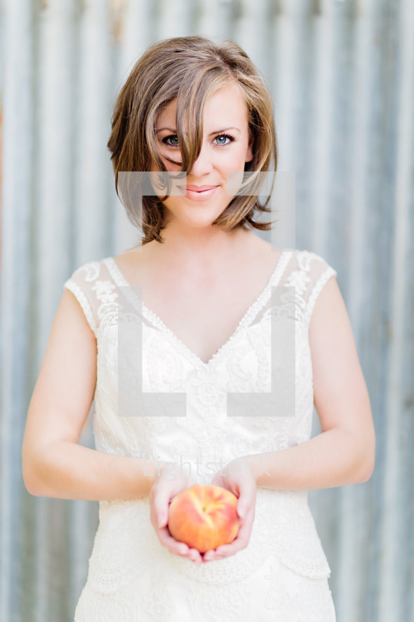 A woman holding a peach. Bride wedding white dress galvanized steel  Brunet brown hair