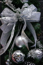 silver bow and ornaments on a Christmas tree