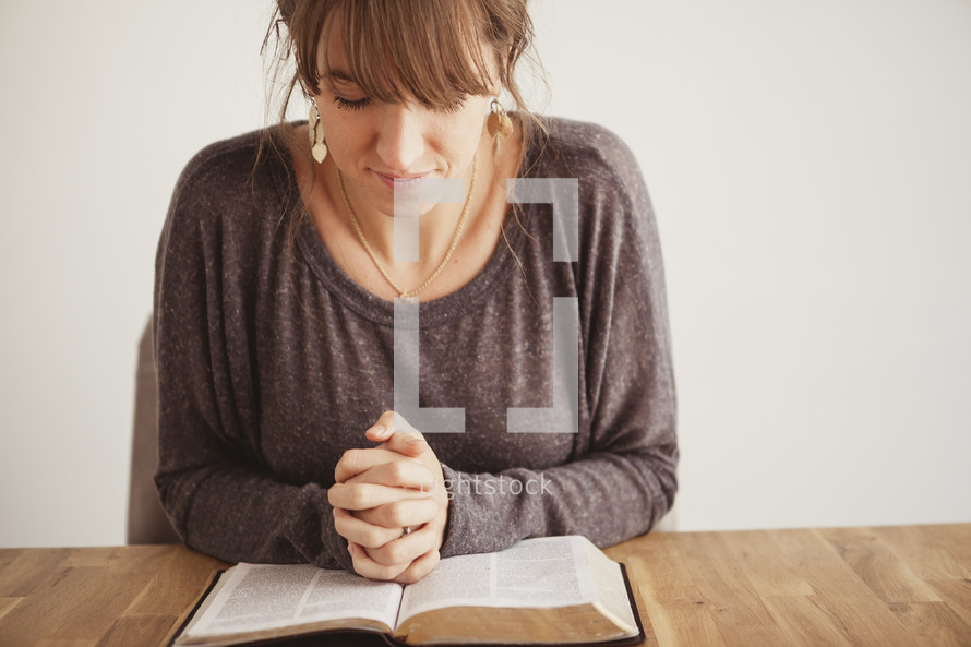 woman with her hands folded in prayer on a Bible
