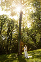 Bride standing in a forest holding flowers