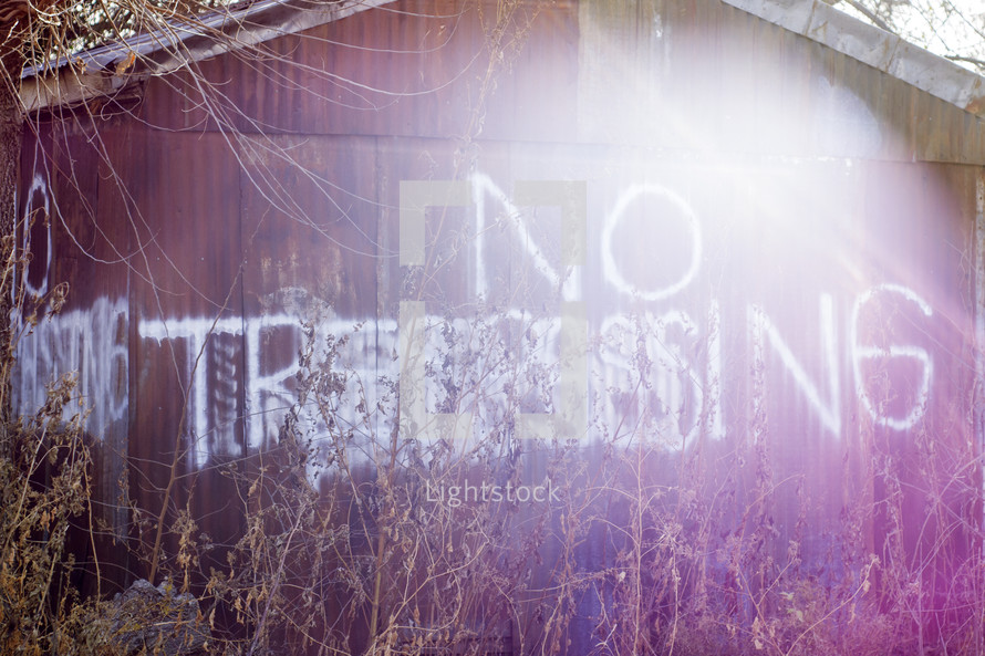 """Rusty barn in tall weeds spray painted with """"no trespassing."""""""