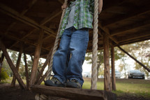 Boy standing on swing
