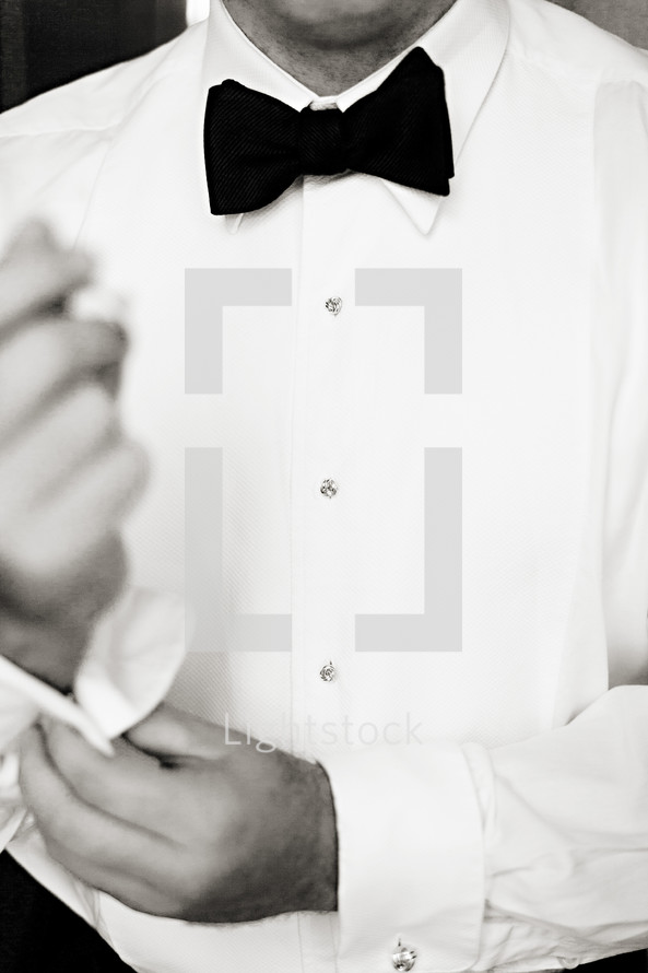 man putting on a tuxedo shirt buttoning sleeve Bow tie