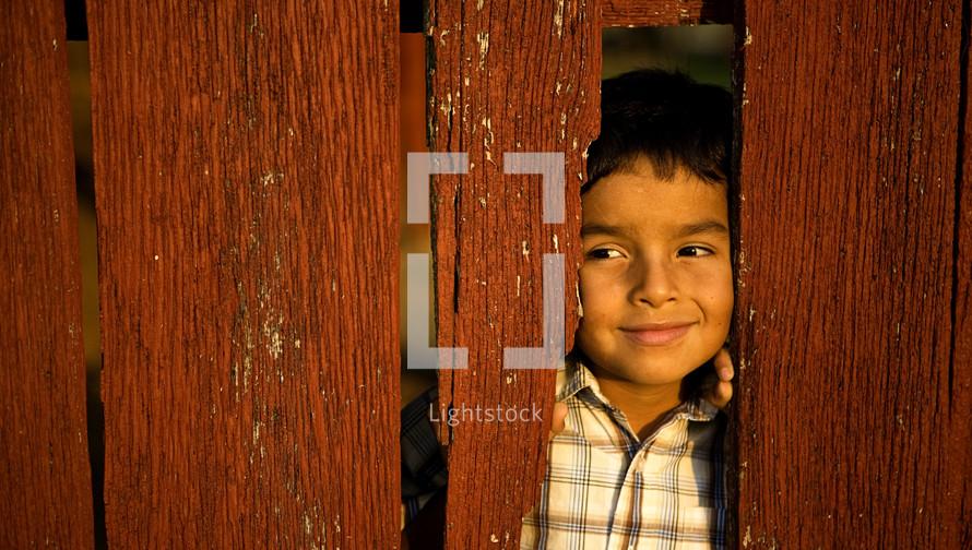 Boy peeking through wood fence