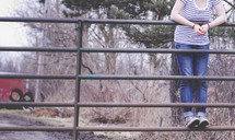 young woman standing on a metal gate