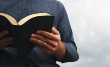 a man reading a Bible outdoors