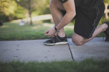 Runner tying his shoe on the sidewalk.