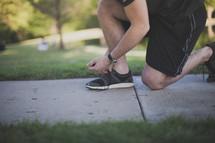 Runner tying his shoe on the sidewalk.