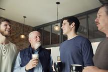 men's group holding coffee mugs