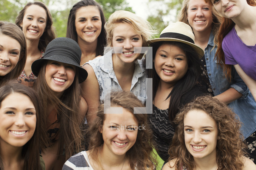 A group of smiling teenage girls together in a group.