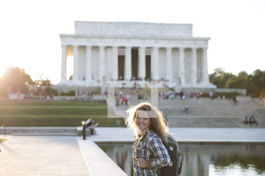 a girl with a back pack standing in front of the Lincoln Memorial.